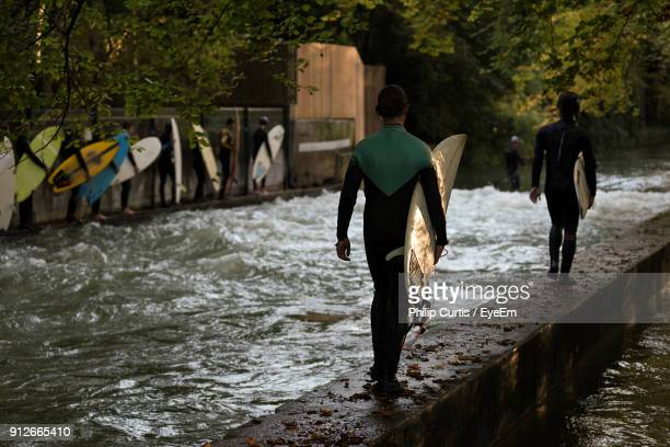 rear view of surfers walking over lake - münchen stock-fotos und bilder
