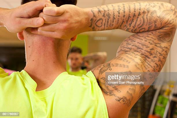 Rear view of tattooed man hands behind head doing stretching exercise