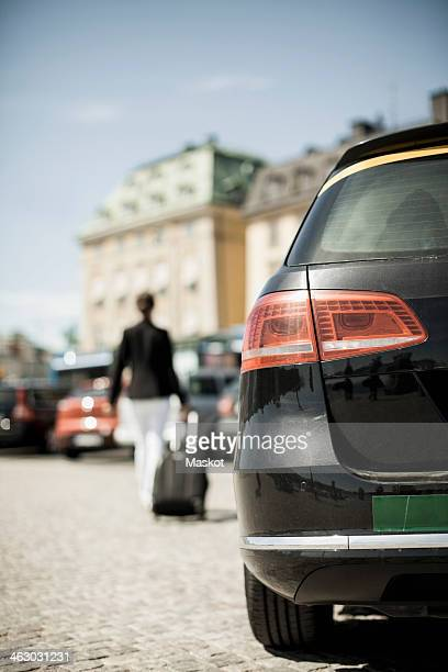 Rear view of taxi with businesswoman dragging luggage in background