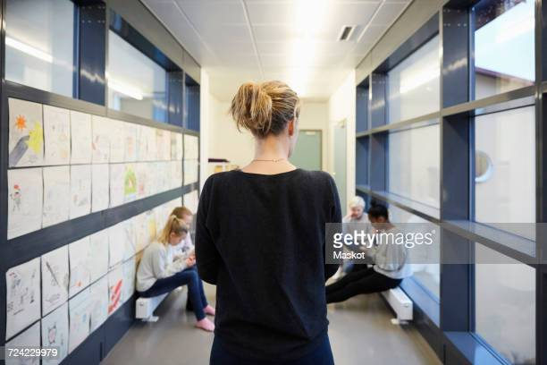 rear view of teacher looking at students in school corridor - school principal stock pictures, royalty-free photos & images