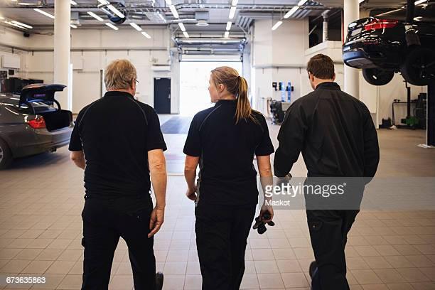 Rear view of team walking in auto repair shop