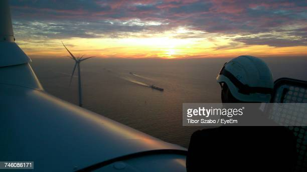 rear view of technician on wind turbine during sunset - marine engineering stock pictures, royalty-free photos & images