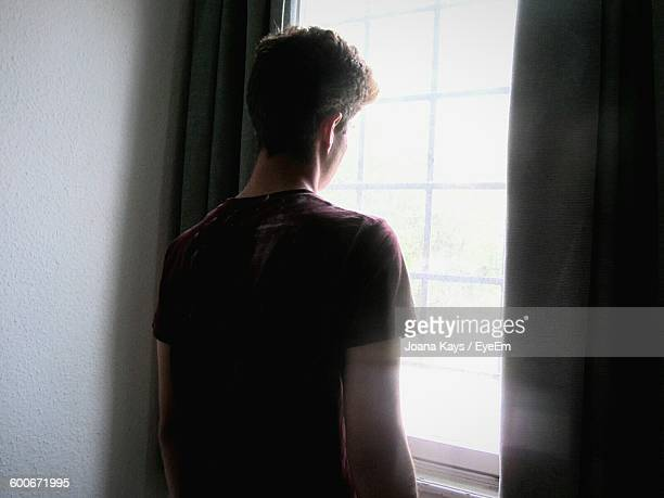 Rear View Of Teen Boy Looking Through Window