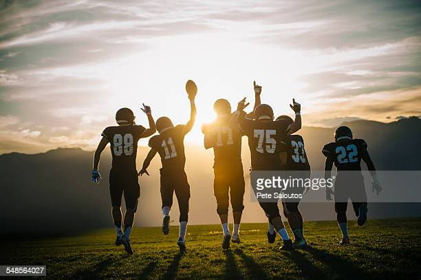 rear view of teenage and young male american football team celebrating at sunset - squadra sportiva foto e immagini stock