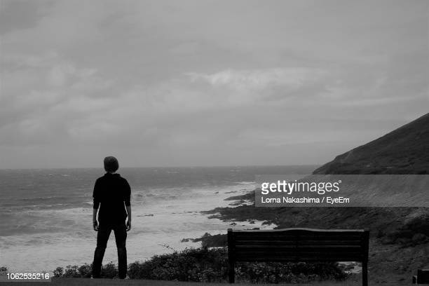 Rear View Of Teenage Boy Standing At Beach Against Sky