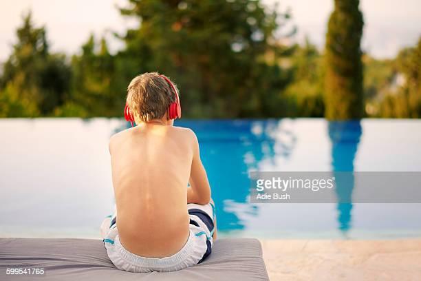 Rear view of teenage boy wearing headphones sitting at infinity pool