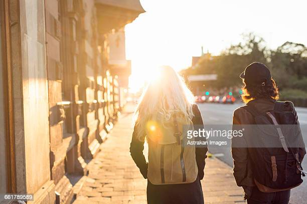 Rear view of teenage friends walking at street during sunset