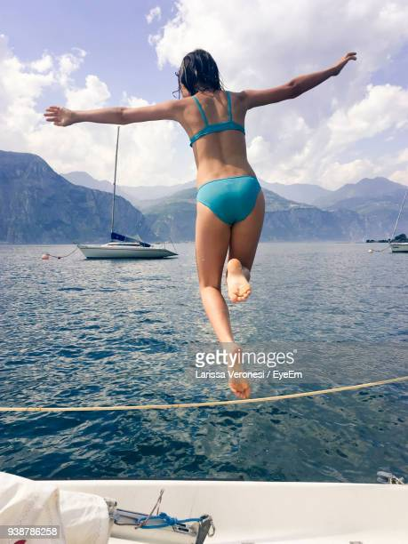 Rear View Of Teenage Girl In Bikini Jumping Into Sea