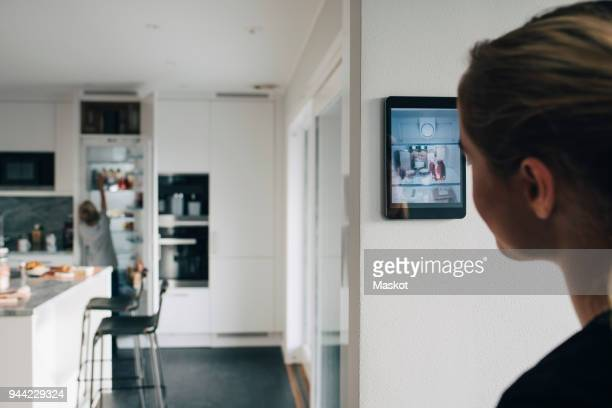 Rear view of teenage girl standing by wall with digital tablet looking at brother in kitchen