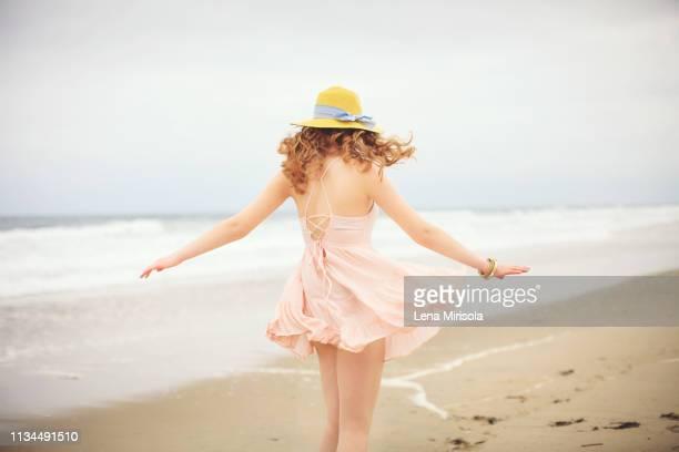 rear view of teenage girl strolling on beach, hampton, new hampshire, usa - サンドレス ストックフォトと画像