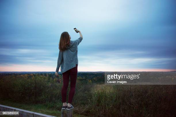 rear view of teenage girl taking selfie at dusk - ノースカロライナ州ローリー ストックフォトと画像
