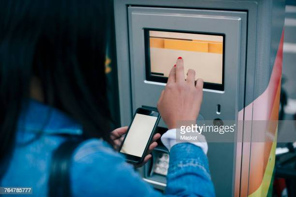 rear view of teenage girl touching atm screen while holding smart phone - gui bildbanksfoton och bilder