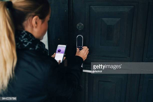 Rear view of teenage girl using smart phone to unlock house door