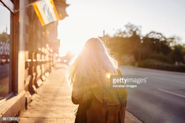 Rear view of teenage girl walking on footpath during sunset