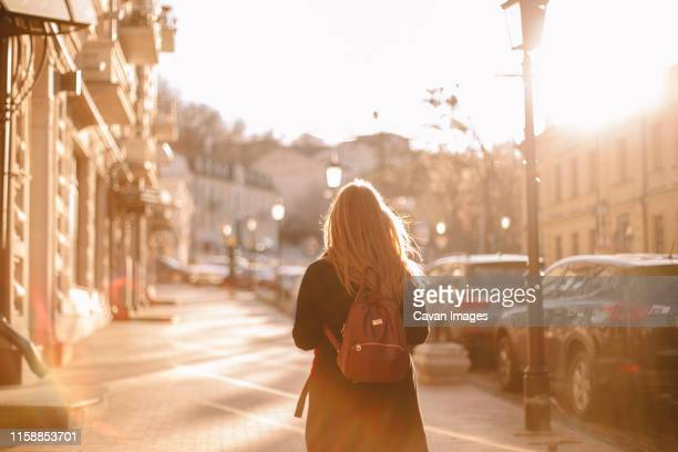 rear view of teenage girl with backpack walking on street - golden hour stock pictures, royalty-free photos & images