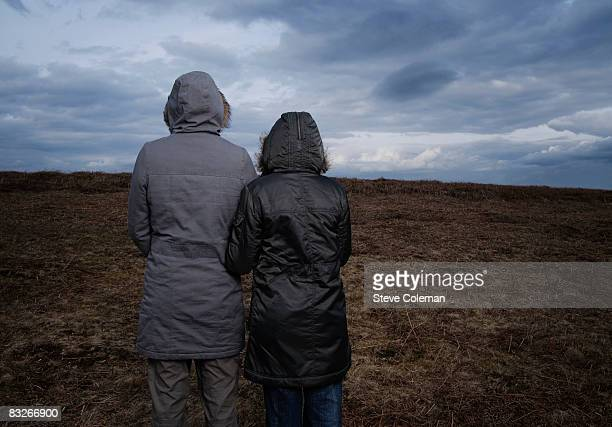 rear view of teenage girls standing in field - parka coat stock photos and pictures