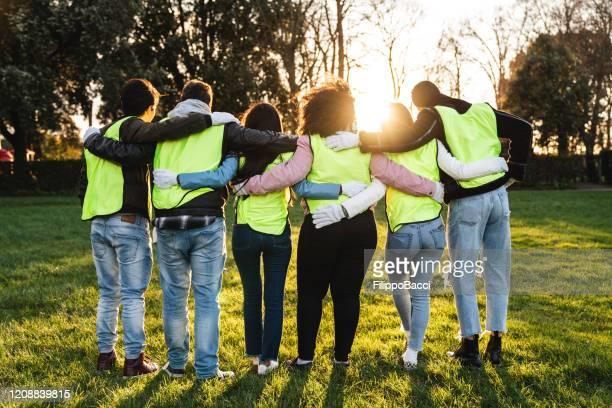 rear view of teenager volunteers embracing together - attività foto e immagini stock