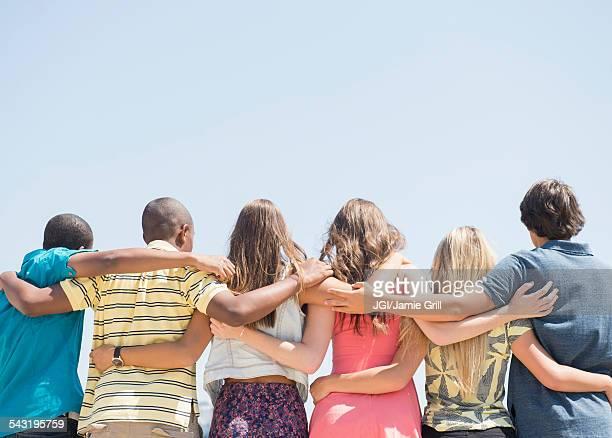 rear view of teenagers hugging under blue sky - igualdad fotografías e imágenes de stock