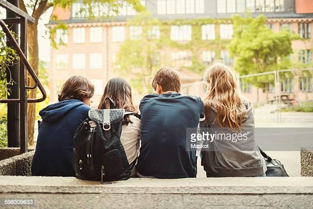 rear view of teenagers sitting on steps outdoors - voortgezet onderwijs stockfoto's en -beelden