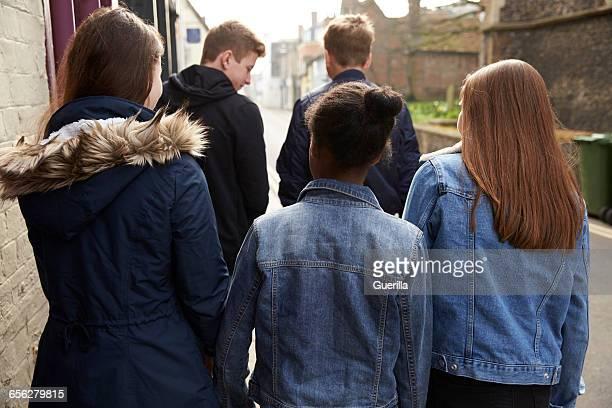 Rear View Of Teenagers Walking Along Urban Street