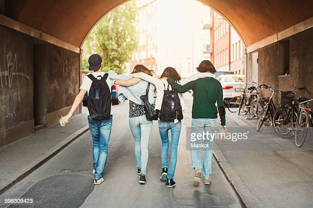 Rear view of teenagers with arms around walking in tunnel