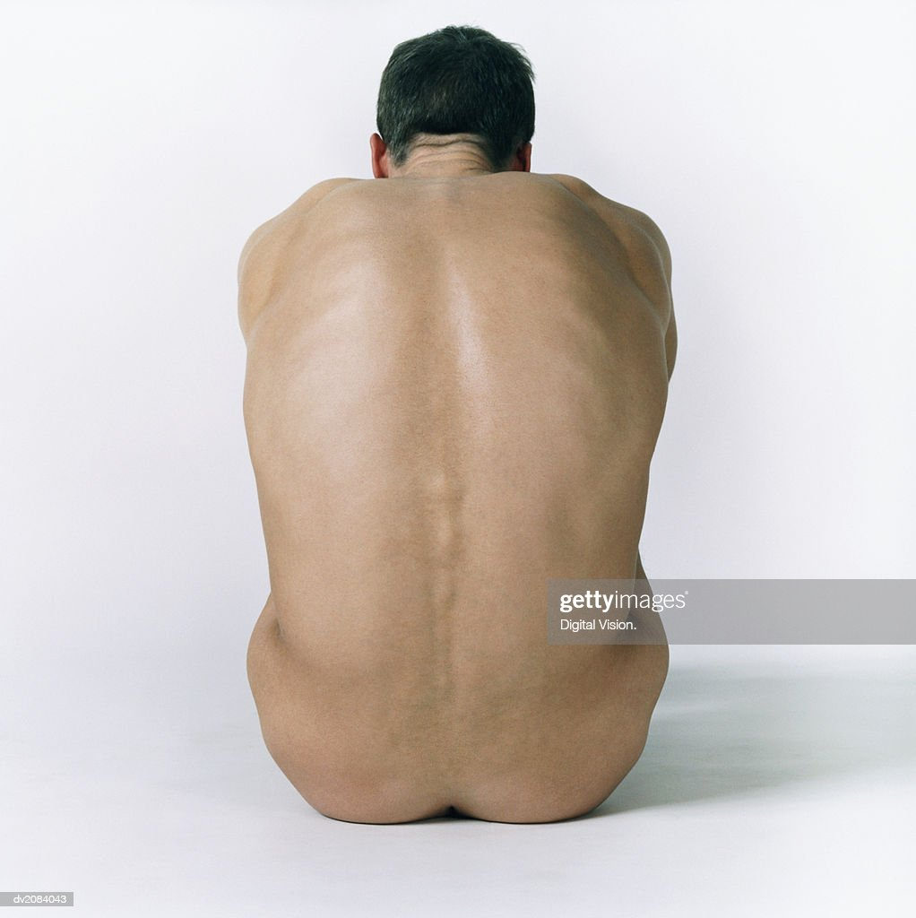 Rear View of the Back of a Naked Man Sitting Down : Stock Photo