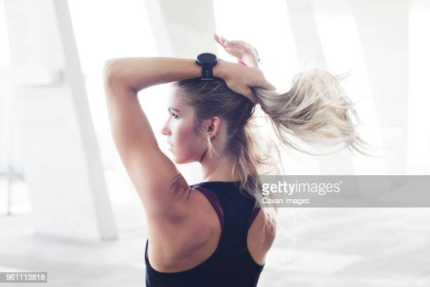 rear view of thoughtful female athlete tying ponytail in parking lot - ponytail stock pictures, royalty-free photos & images