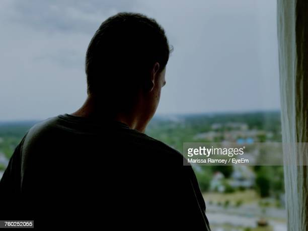 Rear View Of Thoughtful Man Standing Against Window