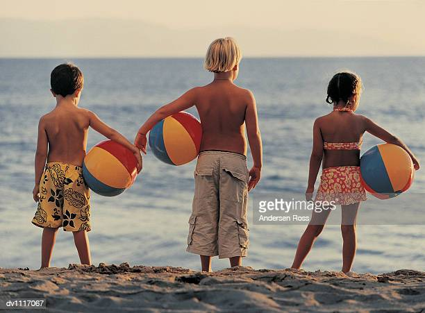 Rear View of Three Children Holding Beach Balls and Looking at the Sea