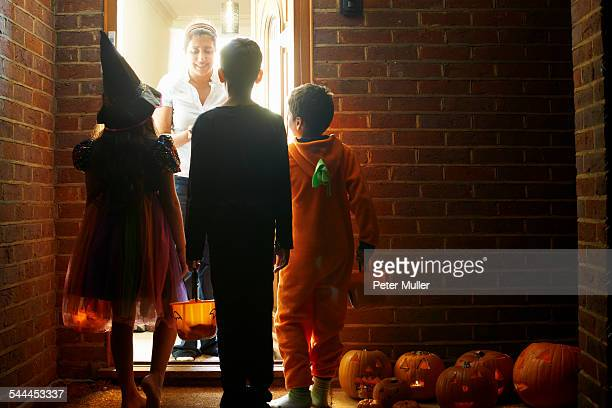 rear view of three children wearing halloween costumes trick or treating - halloween kids stock photos and pictures