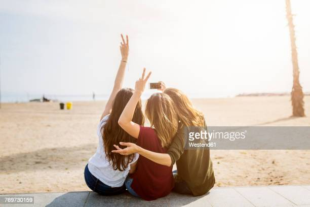 rear view of three female friends sitting at the beach taking a selfie - amizade imagens e fotografias de stock