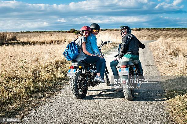Rear view of three friends on motorcycles on rural road, Cagliari, Sardinia, Italy