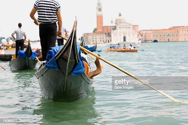 rear view of three gondoliers rowing gondolas, venice, veneto, italy - gondel stock-fotos und bilder