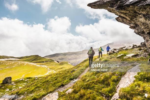 rear view of three hikers hiking beneath rock overhang, fil de cassons, segnesboden, graubunden, switzerland - weitwinkelaufnahme stock-fotos und bilder