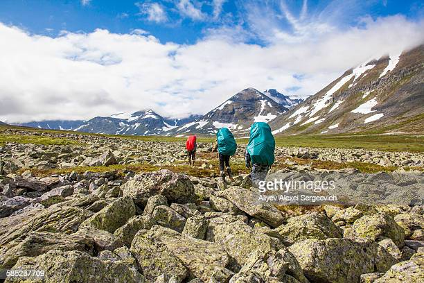 rear view of three hikers hiking valley boulders, ural mountains, russia - summits russia 2015 stock pictures, royalty-free photos & images