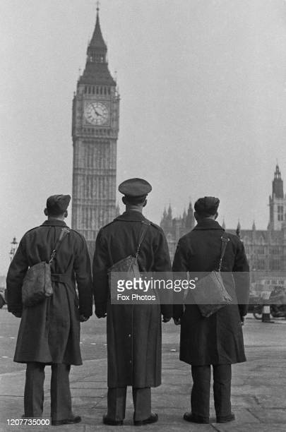 Rear view of three military figures each with a shoulder bag on their back as they face the clock tower home to Big Ben at the Houses of Parliament...