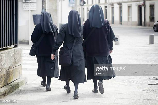 rear view of three nuns walking in the street. - nun stock pictures, royalty-free photos & images