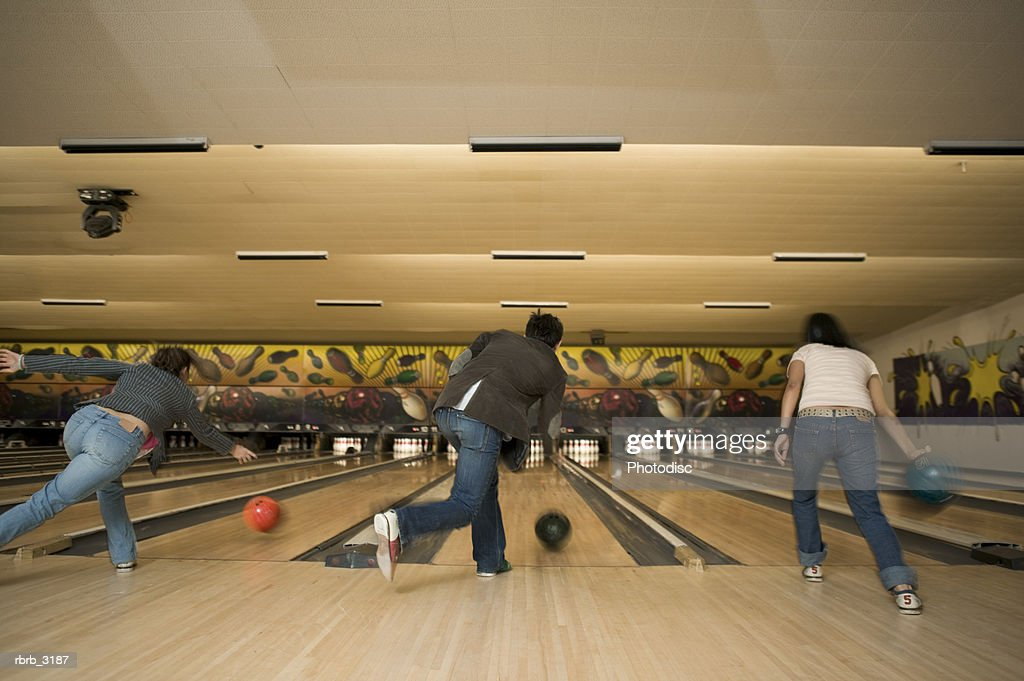 Rear view of three people bowling at a bowling alley : Stockfoto