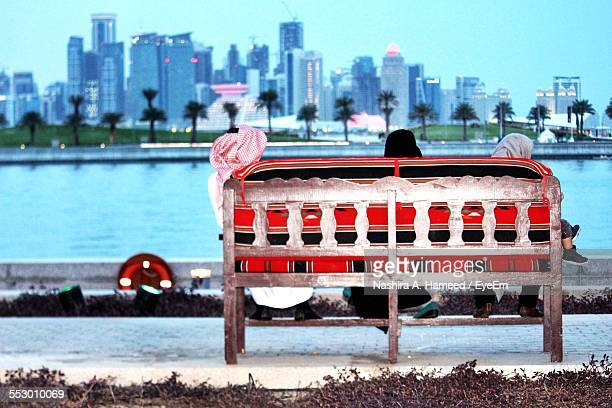 Rear View Of Three People Sitting On Bench Looking At View