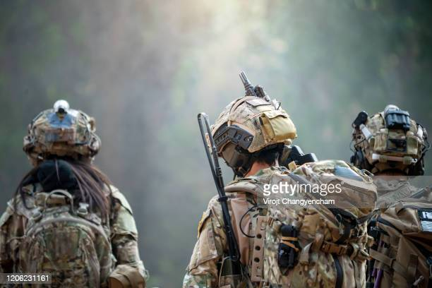 rear view of three soldiers patrolling along the risky area. - terrorism stock pictures, royalty-free photos & images