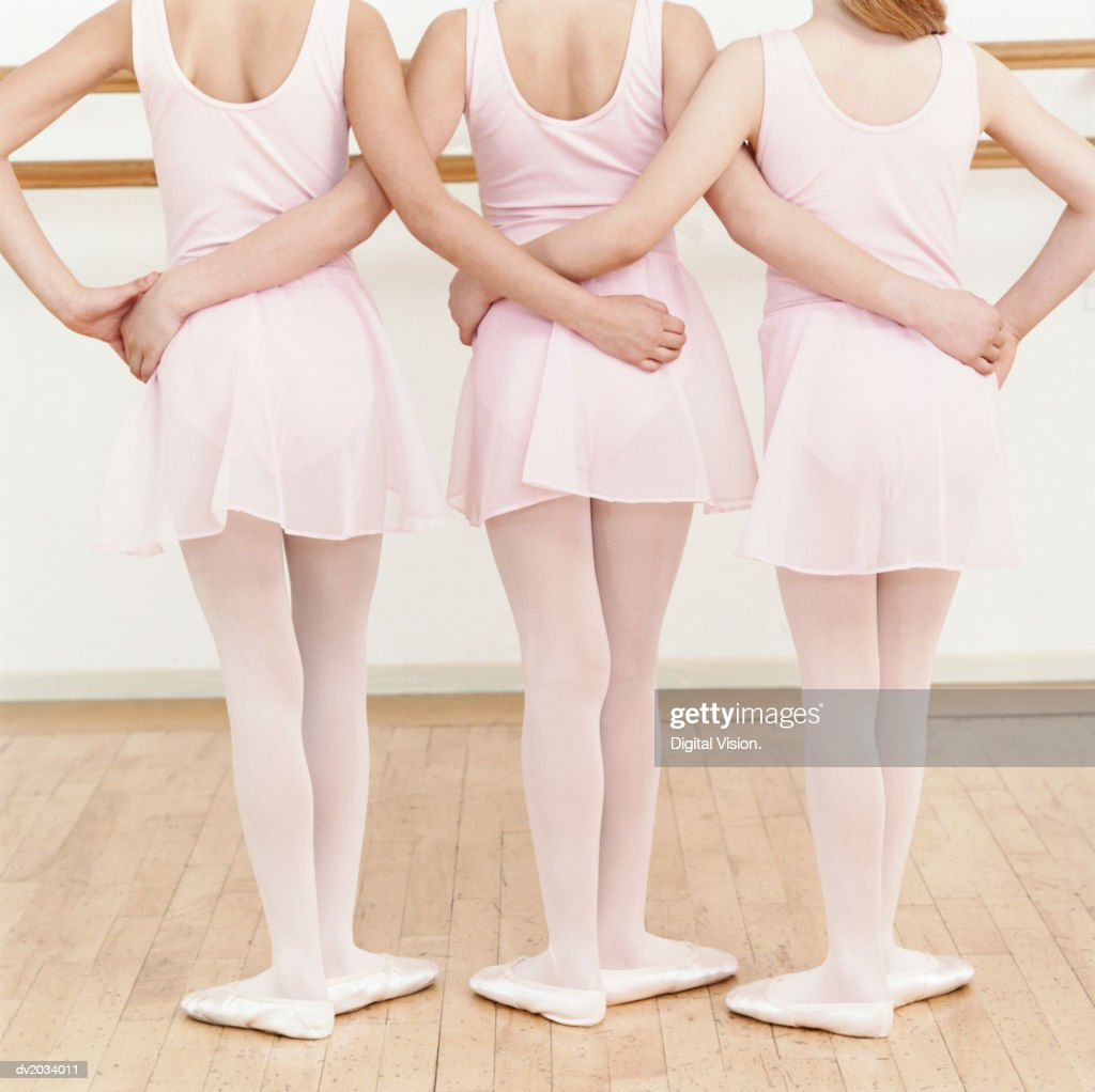 Rear View of Three Young Ballet Dancers Standing in a Line With Their Arms Around Each Other : Stock Photo