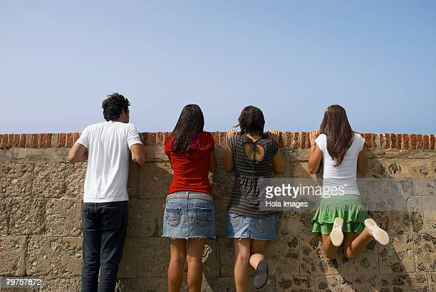 rear view of three young women and a young man looking over a stone wall, morro castle, old san juan, san juan, puerto rico - old san juan wall stock photos and pictures