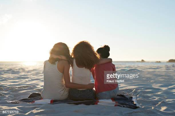 rear view of three young women sitting on beach - 休日 ストックフォトと画像
