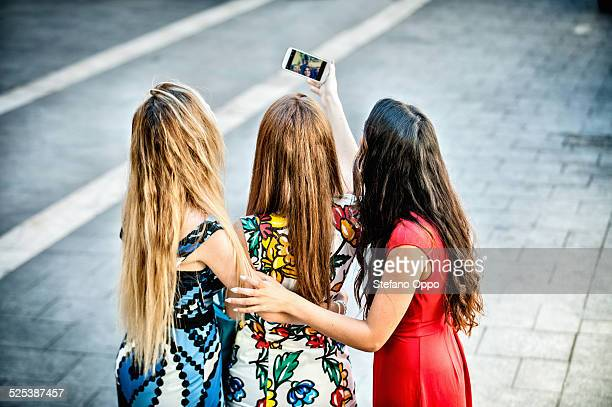 Rear view of three young women taking selfie with smartphone, Cagliari, Sardinia, Italy
