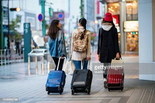 スーツケースが付いている都市を歩く 3 人の若い女性の後姿 - 観光 ストックフォトと画像
