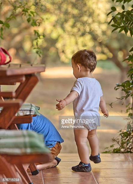 Rear view of toddler boy with arms outstreched
