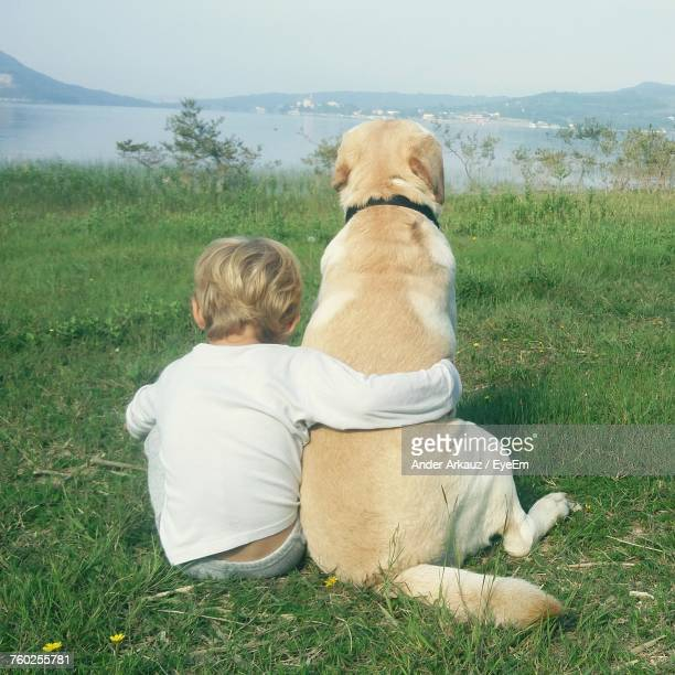 Rear View Of Toddler Holding Dog