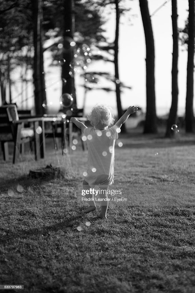 Rear View Of Toddler With Arms Raised, Walking In Grass, Soap Bubbles In Foreground : Foto stock