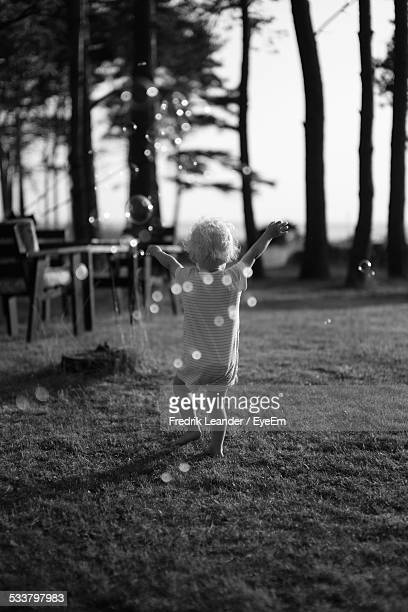 rear view of toddler with arms raised, walking in grass, soap bubbles in foreground - leander licht stock-fotos und bilder
