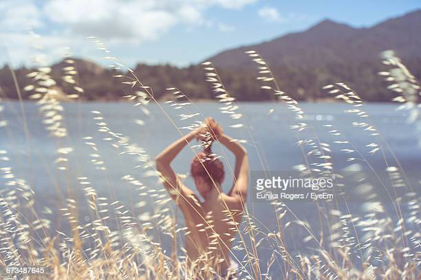 Rear View Of Topless Woman Tying Hair While Standing Against Lake